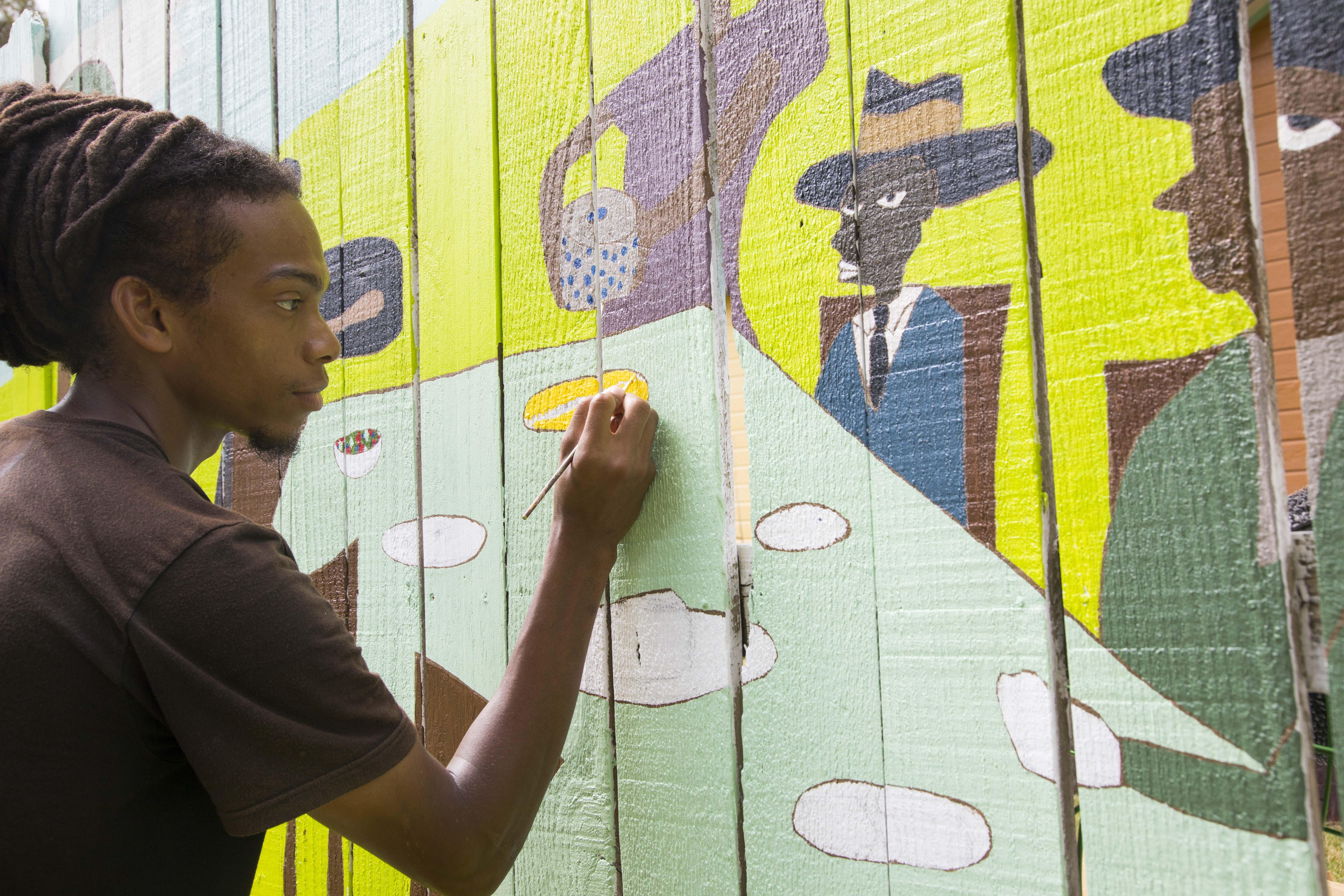 Local resident artist Hotep finishes 40' mural in the Grenada Street Folk Garden!